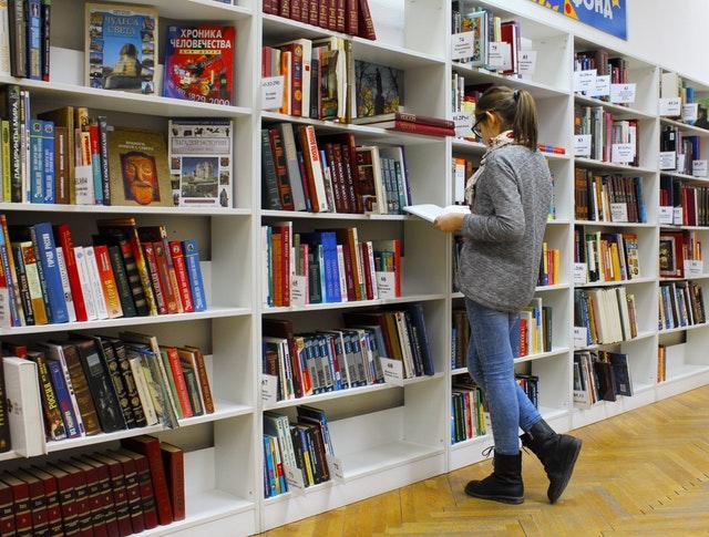 סטודנטית מחפשת את כללי כתיבת ביבליוגרפיה בסיפריה