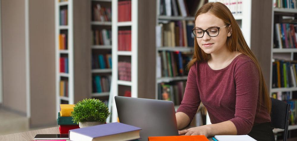 סטודנטית כותבת עבודות סמינריון בספריה